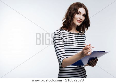 Crucial notes. Beautiful auburn-haired young woman writing on a sheet pinned to a holder while smiling at the camera
