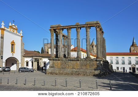 Evora Portugal - June 2 2017: Roman ruins of Diana's Temple and the chapel of Saint John the Evangelist. The dome of the cathedral in the background