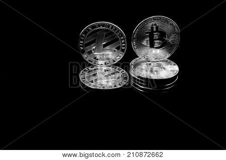 On a black background with free text space are silver coins of a digital crypto currencies - Litecoin and Bitcoin. In addition to the lying coins there are standing bitcoin and litecoin.