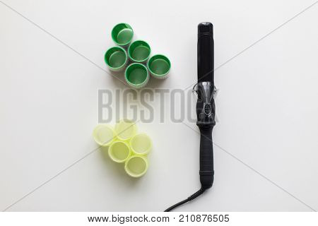 hair tools, beauty and hairdressing concept - curling iron or hot styler and curlers on white background