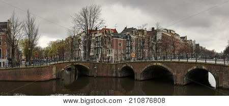 Amsterdam, Netherlands - April 9, 2012. Bridges and houses of Amsterdam on a cloudy day. Crossing the streets of Keizersgracht and Reguliersgracht in the historical part of the city.