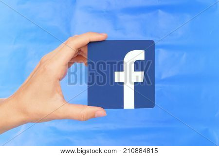 Kiev Ukraine - September 4 2017: Hand holds Facebook icon printed on paper on blue paper background. Facebook is a well-known social networking service