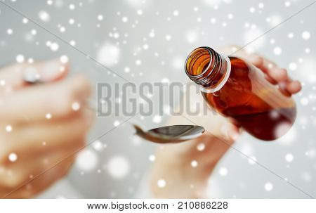 healthcare, people and medicine concept - woman pouring medication or antipyretic syrup from bottle to spoon over snow