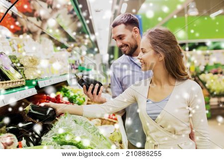shopping, food, sale, consumerism and people concept - happy couple buying avocado at grocery store or supermarket over snow