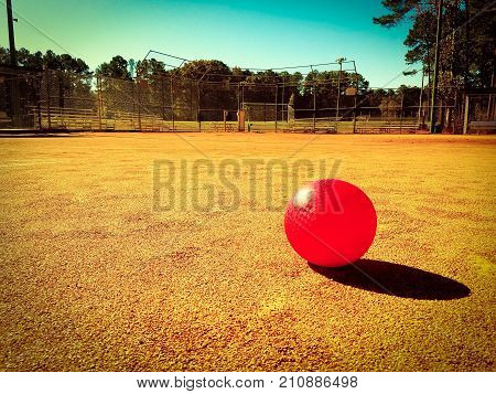 A red kickball on a dirt playing field with a light vignette. Copy space.