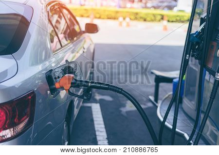 Gas nozzle pumping gas into a gray blonde car to fill the machine with fuel. Gas station pump.