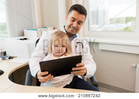 medicine, healthcare, pediatry and people concept - happy doctor or pediatrician holding little girl patient with tablet pc computer in medical office at clinic poster