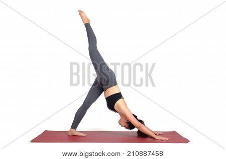 young asian woman doing yoga in Eka Pada Adho Mukha Svanasana or One-Legged Downward-Facing Dog pose on mat isolated on white background exercise fitness sport training healthy lifestyle concept