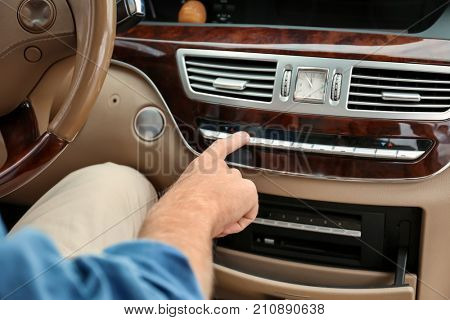 Young man turning on air conditioning system in car