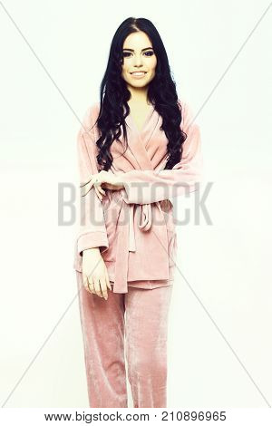 pretty cute sexy girl or beautiful woman with fashion makeup on smiling happy face and curly long hair posing in womans pink velour pajama home suit isolated on white background