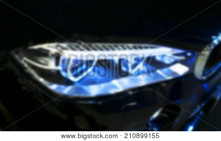 Headlight of a modern sport car. Front view of luxury sport car. Car exterior details. The front lights of the car. Soft lightning