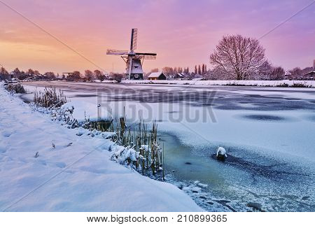 Dutch Windmill In The Snow Of A Holland Winter