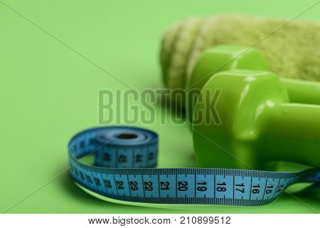 Tape measure in cyan blue color near barbells close up. Sports regime equipment. Athletics and weight loss concept. Dumbbells in bright green color twisted measure tape and towel on green background