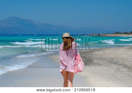 Young girl in a straw hat on the beach enjoying the beautiful view. View from the back.