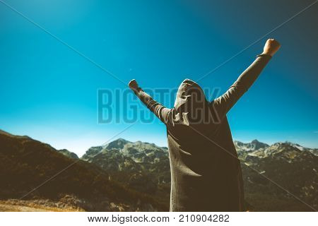 Victorious female person standing on mountain top with arms raised in V. Winning and success. Achievement and accomplishment in life. Toned image.