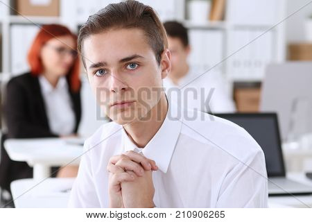 A young businessman at the meeting folded his hands and prayed that he was not punished at the meeting looks pathetic and confused because of a mistake and very afraid of being fired for his career.