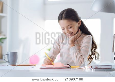 My home task. Delighted positive cheerful girl sitting at the table and doing her home task while sitting in her room