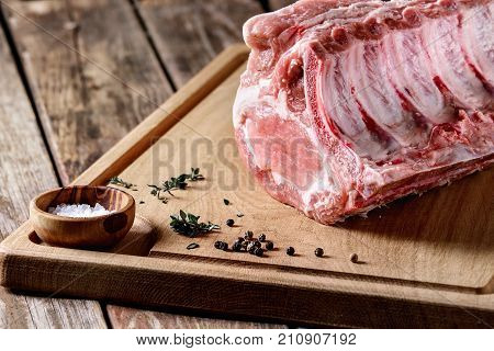 Fresh raw uncooked whole rack of pork loin with ribs on wooden cutting board with salt, thyme and butcher clever over old wood plank table. Close up.