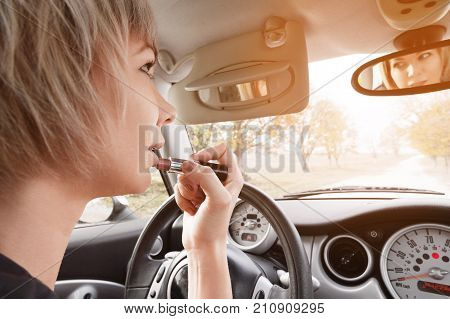 Cute blond woman with short hair coloring lips while sitting at the wheel of her car. The concept of driving a woman. Inappropriate driving lessons. Distraction from driving