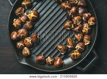 Roasted chestnuts in cast iron grilling pan over dark scorched wooden background, top view, copy space