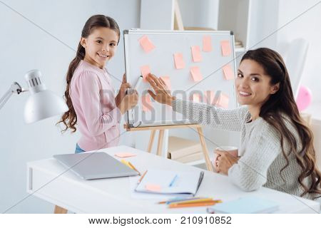 Let me take one. Nice cheerful positive woman holding a cup of coffee and taking a sticky note from the whiteboard while looking at you