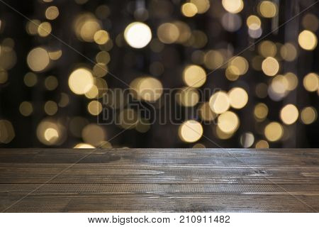 Blurred Gold Garland And Wooden Tabletop As Foreground. Image For Display Or Montage Your Christmas