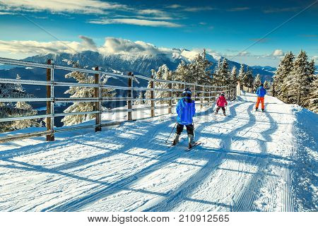 Stunning winter landscape with wonderful Bucegi mountains in background and skiers on the ski slopes, Poiana Brasov ski resort, Transylvania, Romania, Europe