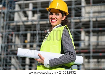 Female civil engineer with construction plans at building site of high-riser