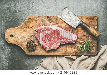 Flat-lay of raw prime beef meat dry-aged steak rib-eye on bone with seasoning and chopper knife on wooden cutting board over grey concrete background, top view. Meat high-protein dinner concept
