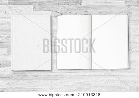 Blank white notebook cover with open notebook page on white wooden table with clipping path on notebook for mockup design