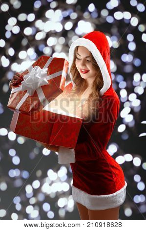 Smiling Snow Maiden in the red sexy suit opens a big gift for New Year 2018, 2019 and Christmas. A girl has curvy, sexy figure, long curly hair and bright lipstick. She stands on the agleam background.