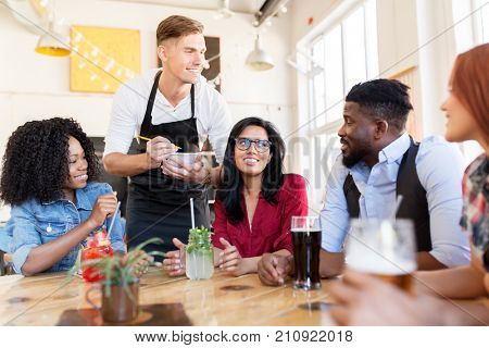 service and people concept - group of happy international friends with drinks and waiter with notepad receiving order at bar or restaurant