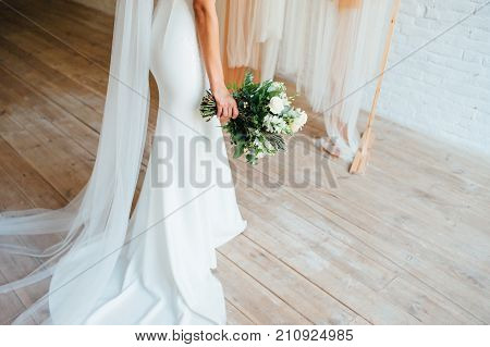 Closeup of beautiful bridal bouquet of fresh flowers in hands of young bride ready for wedding ceremony. Woman wearing gorgeous luxury white dress
