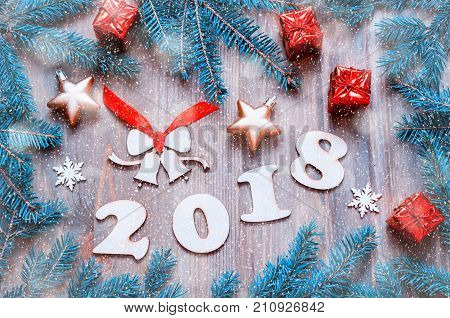 New Year 2018 background with 2018 figures Christmas toys blue fir tree branches and snowflakes. New Year 2018 still life. Happy New Year 2018 postcard