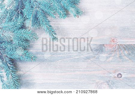 Winter background. Winter blue fir tree branches with winter snowflakes on the wooden background. Winter still life, free space for text. Winter fir tree branches on the wooden backgorund, winter concept. Winter still life