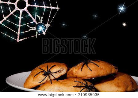 Fun Halloween spider food. Trick or treat spooky party snacks with fantasy cartoon style creepy background. Novelty plastic spiders on cookie muffins with sparkling spider web over a night sky with stars.