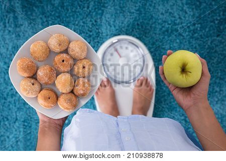High Angle View Of A Person Holding Cookies And Apple Standing On Weighing Scales