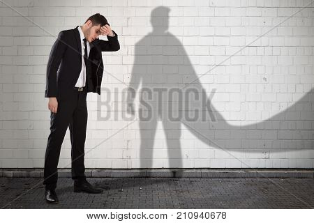 Young Tired Businessman With His Own Shadow In Superhero Cape