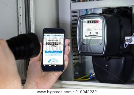 Close-up Of A Man's Hand Holding Mobile Phone Showing Electric Meter Reading And Holding Flashlight
