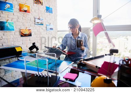 Young person, small business, technology. Busy woman working as photographer in studio, holding coffee mug. Girl with computer laptop for photo editing. Artist doing art production