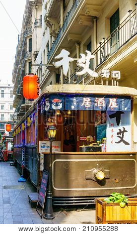 Shanghai, China - Nov 6, 2016: On Jiujiang Road, near Nanjing Road Pedestrian Street - Modern buildings in western architectural designs. A railway carriage converted to a restaurant.