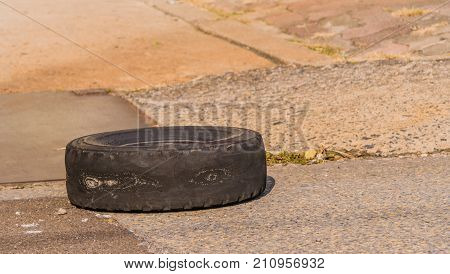 Closeup of old tire without tread and showing sever signs of wear laying on pavement next to concrete walkway