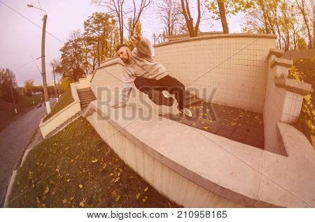 A Young Guy Performs A Jump Through The Concrete Parapet. The Athlete Practices Parkour, Training In