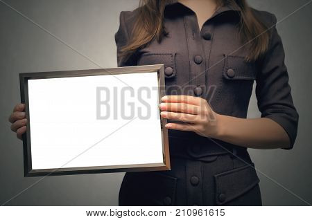 Grateful letter. Gratitude concept. Accolade. Thank letter. Special offer. Young business woman in strict dress holding in hands empty blank photo frame. Appreciation document.