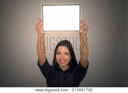 Grateful letter. Gratitude concept. Accolade. Thank letter. Special offer. Young business woman in strict dress holding in hands empty blank photo frame above the head. Appreciation document.
