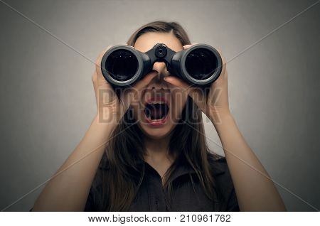 Young woman looking through binoculars with her wide open mouth. Find and search. Find something interesting.