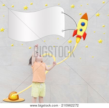 Closeup cute asian kid point to space in text box with cute rocket cartoon on marble stone wall textured background