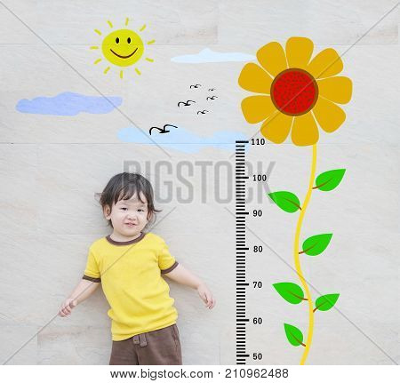 Closeup happy asian kid stand for measure height with cute cartoon sunflower at the marble stone wall textured background