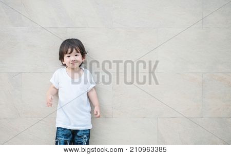 Closeup happy asian kid with smile face on marble stone wall textured background with copy space