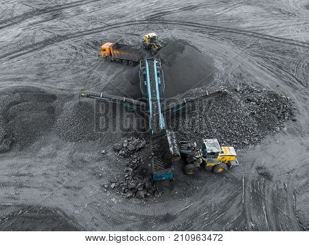 Open pit mine, breed sorting. Mining coal. Bulldozer sorts coal. Extractive industry, anthracite. Crushing marshalling complex. Coal industry. Black gold